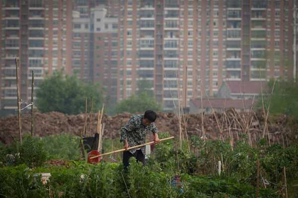 China has launched a debt-for-bond swap program aimed at giving provinces and cities some breathing room in repaying debts. A Chinese peasant farms a field in suburb in Wuhan, Hubei.